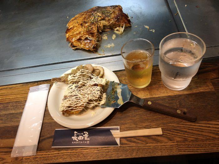 Okonomiyaki på tallrik med dryck bredvid